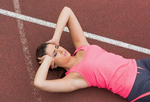 Mulher deitada após sofrer com nauseas e tonturas frequentes durante exercícios