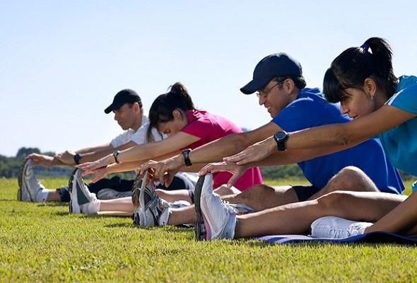 Atletas em um gramado verde, praticando Qual a importância dos exercícios de aquecimento para uma corrida