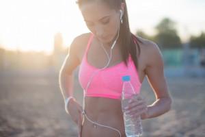 Mulher se hidratando após praticar para melhorar o pace