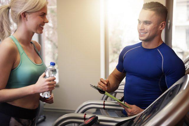 Mulher conversando com seu personal trainer sobre seus treinos para iniciantes na academia