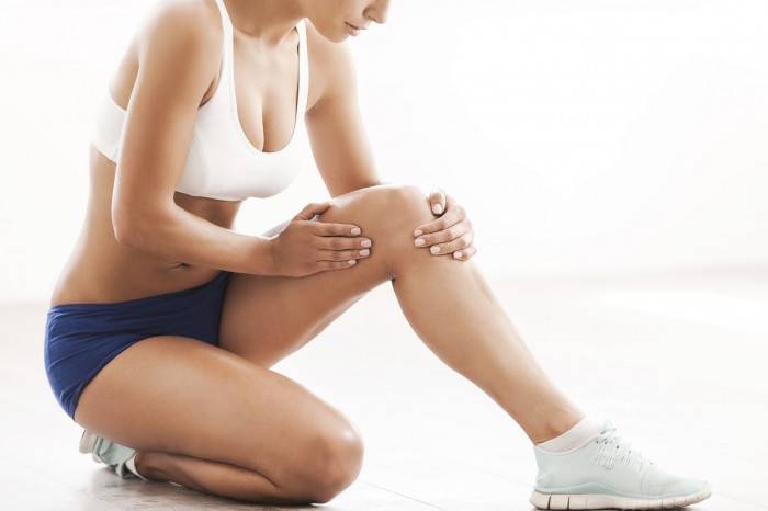 Mulher agachada no chão tentando descobrir se possui lesões nos joelhos