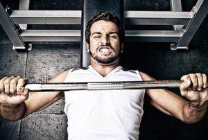 Homem fazendo supino em alguma academia, dando exemplo de como não desistir de fazer musculação na academia.