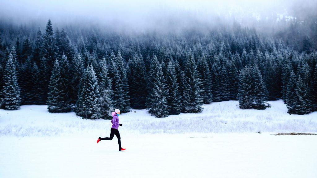 Mulher começando a correr no inverno numa paisagem de floresta com neve