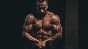 Homem com músculos definidos mostrando como ganhar massa muscular.