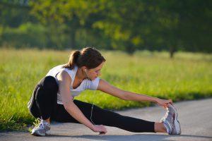 Mulher se alongando depois de aprender o que não fazer antes de correr?