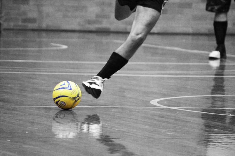Jogador de futsal exemplificando os esportes em quadra.